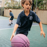 boy dribbling basketball outside