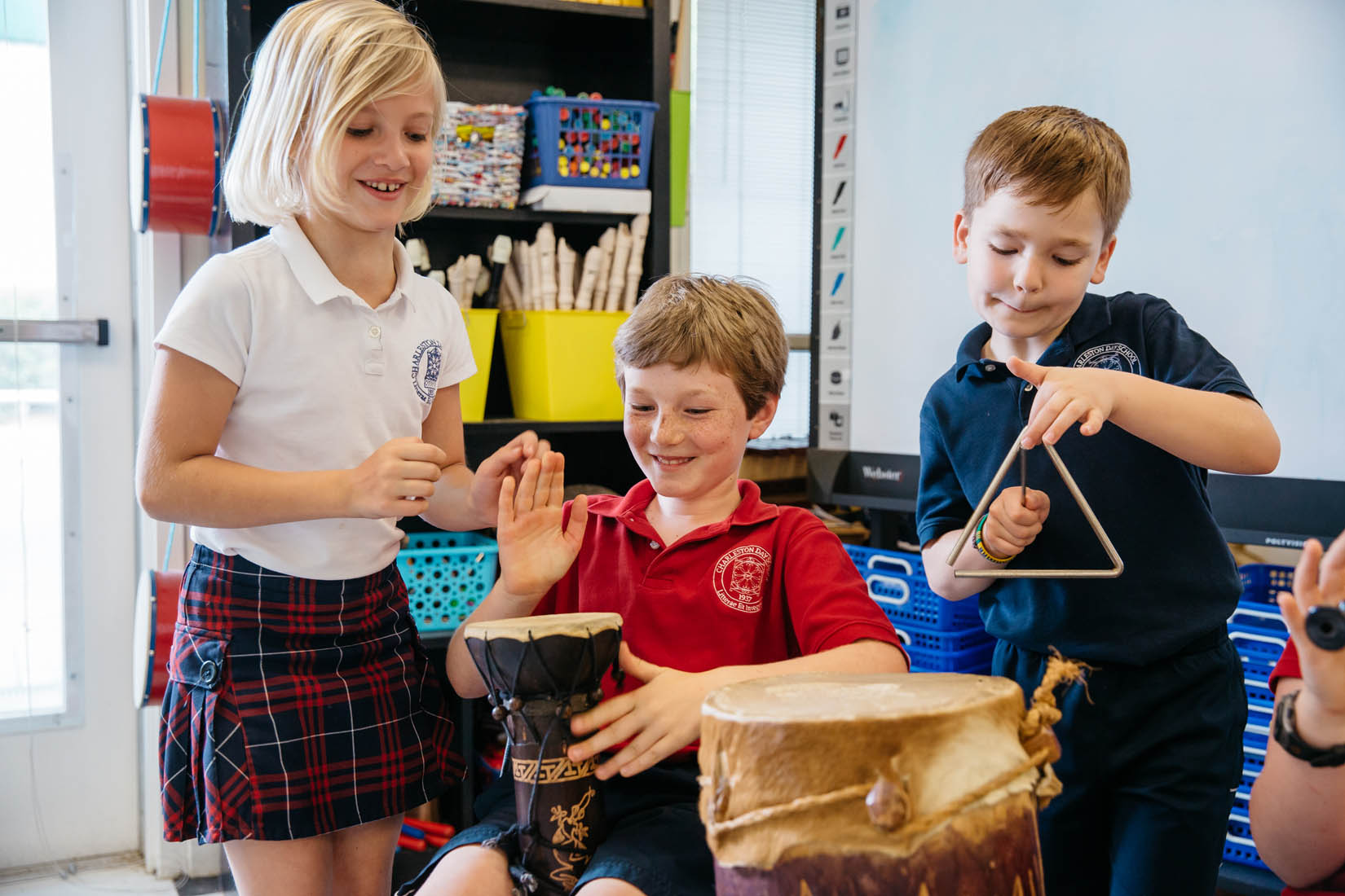 three students make music with drum and triangle