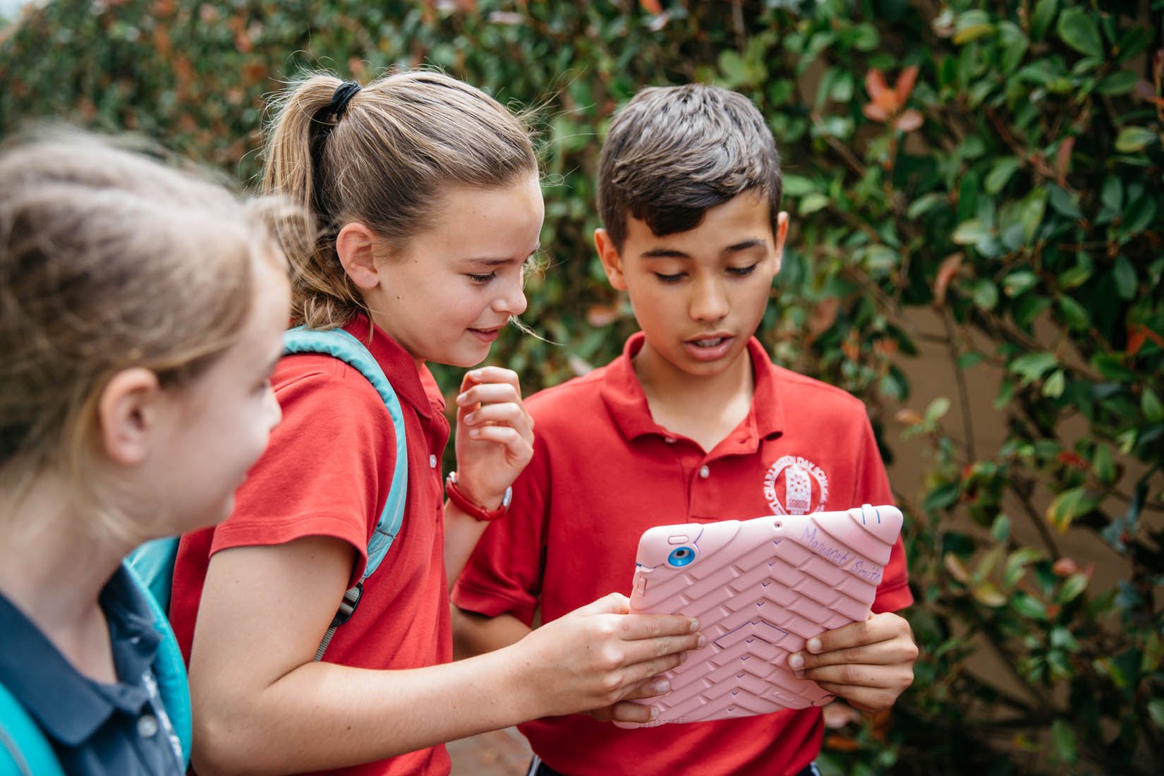 students outside look at ipad