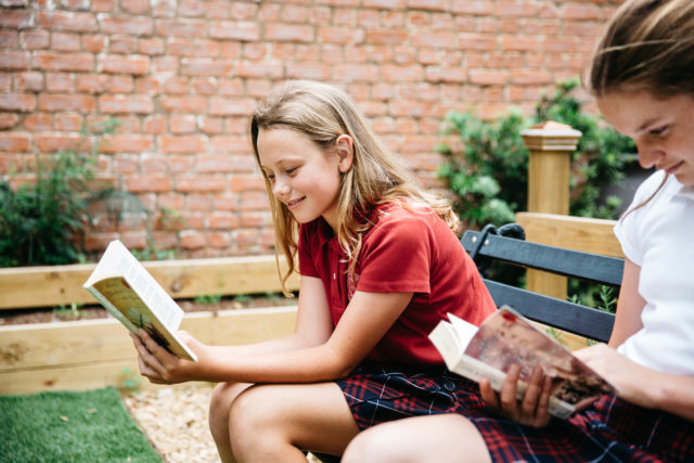 students read book outside in garden