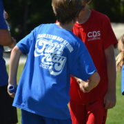 field day students from red and blue shake hands