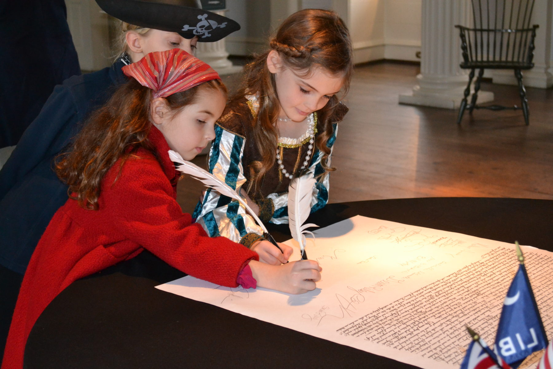 two girls in costume signing a document