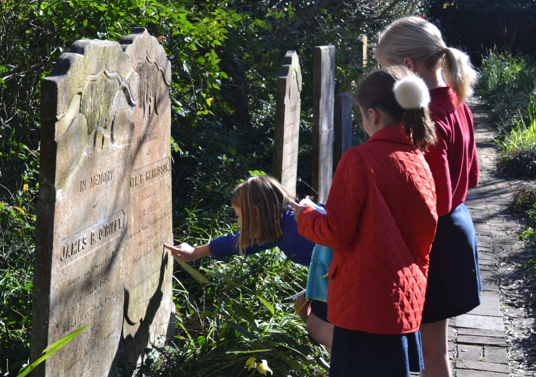 students inspect headstone in cemetary