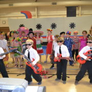 four 2nd graders with guitars perform around the world