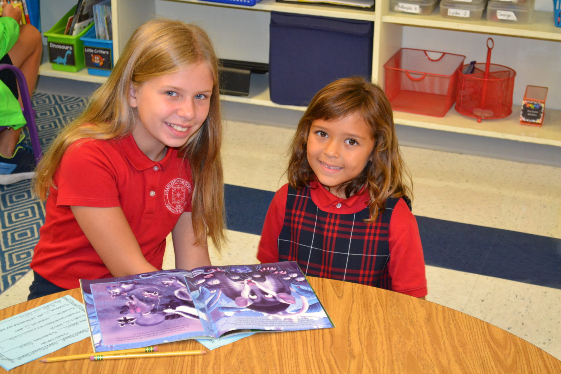 big and little students reading together