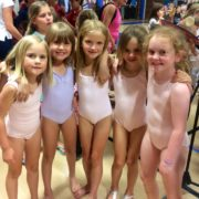 five young gymnasts pose for a photo