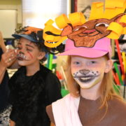 student in face paint prepares for performance 4th grade lion king french